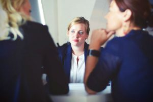 Woman Seated at Table Pitching Business Plan to Two People